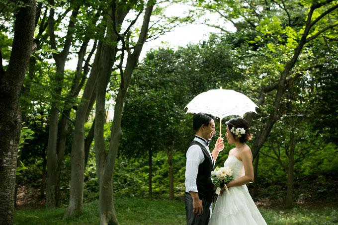 根岸森林公園の森の中で傘から降り注ぐ光を浴びる新郎新婦