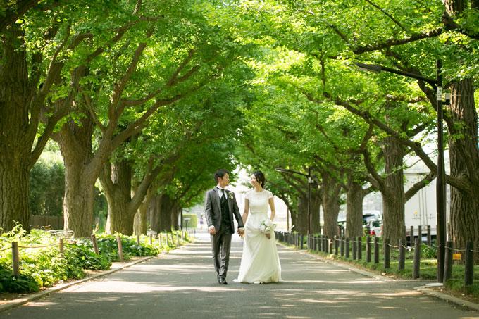 銀杏並木の新緑に囲まれて手をつなぐ新郎新婦のロケーションフォト