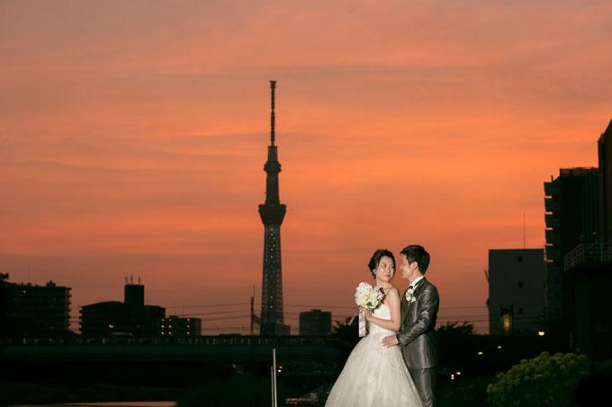 旧中川の河川敷で夕映えに染まる空と東京スカイツリーのシルエットを背景に結婚写真を撮影