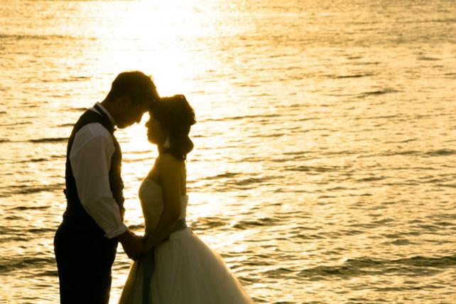 茜色に輝く海にふたりのシルエットが浮かぶロマンチックなロケーションフォト